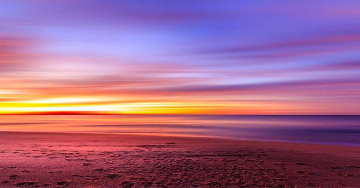 Photo that looks like a painting of the sky at sunset. The beach is in the foreground with footprints in the sand, and the water, sunrise, and dawning sky look like paint brushings across the page.